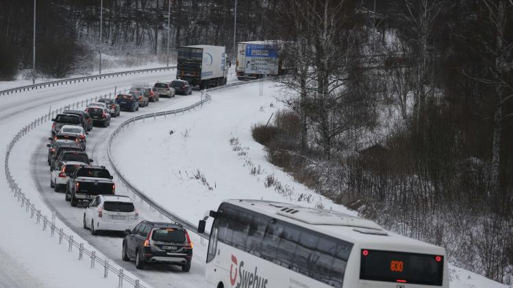 A long line of vehicles are seen along a slippery road west of Ulricehamn