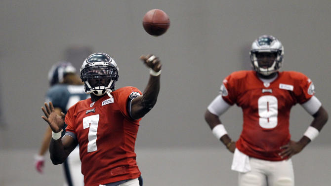 Philadelphia Eagles quarterback Michael Vick, left, throws the ball as quarterback Vince Young watches during practice at their NFL football training facility Wednesday, Oct. 12, 2011 in Philadelphia. (AP Photo/Alex Brandon)