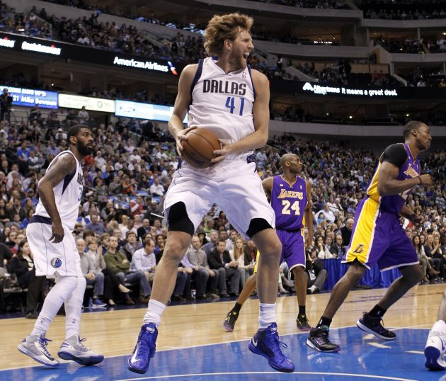 Mavericks' Nowitzki grabs a rebound next to Mayo and Lakers' Howard during the first half of their NBA basketball game in Dallas