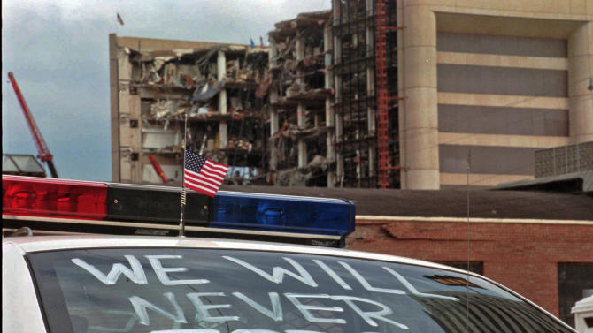"FILE - In this April 24, 1995 file photo, an Oklahoma City police car decorated with the words ""We will never forget"" and a small American flag sits near the Alfred P. Murrah Federal Building in Oklahoma City. On Thursday, July 31, 2014, the FBI capped off its attempt to persuade a federal judge in Salt Lake City that it is not hiding unreleased surveillance videos from the 1995 Oklahoma City bombing by bringing witnesses who testified that there has never been any security-camera videos of the bomb going off. (AP Photo/Rick Bowmer, File)"
