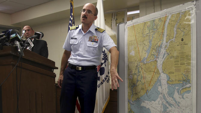 Deputy Commander of Coast Guard Sector New York Capt. Gregory Hitchen gestures towards a map of New York Harbor while speaking at a news conference in New York, Wednesday, June 20, 2012. Similarities in a caller's voice and phrasings have led the Coast Guard to believe there's a link between a hoax distress call reporting a yacht explosion off New Jersey and a mayday call in Texas last month.  (AP Photo/Seth Wenig)