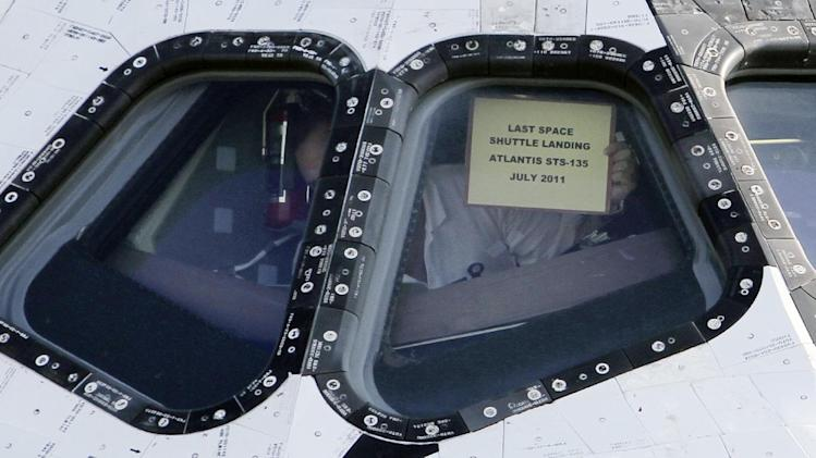 In this Thursday, July 21, 2011 photo, a worker hangs a sign in a window of the space shuttle Atlantis after it landed at the Kennedy Space Center in Cape Canaveral, Fla. It was on view to employees and the media. The landing of Atlantis brought the space shuttle program to an end. (AP Photo/J Pat Carter)