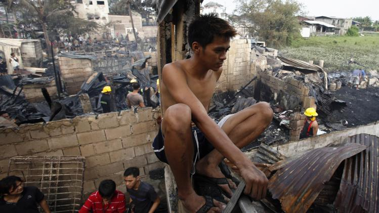 A resident sits on the window of his house destroyed by a fire in Malabon, Metro Manila