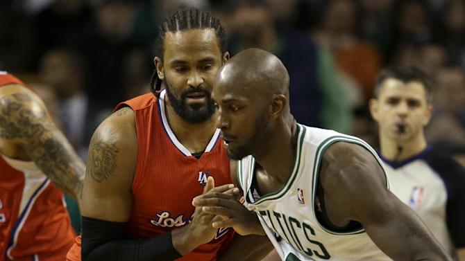 Boston Celtics forward Kevin Garnett (5), right, tries to drive toward the basket past Los Angeles Clippers center Ronny Turiaf , left, of France, in the second quarter of an NBA basketball game in Boston, Sunday, Feb. 3, 2013. The Celtics defeated the Clippers 106-104. (AP Photo/Steven Senne)