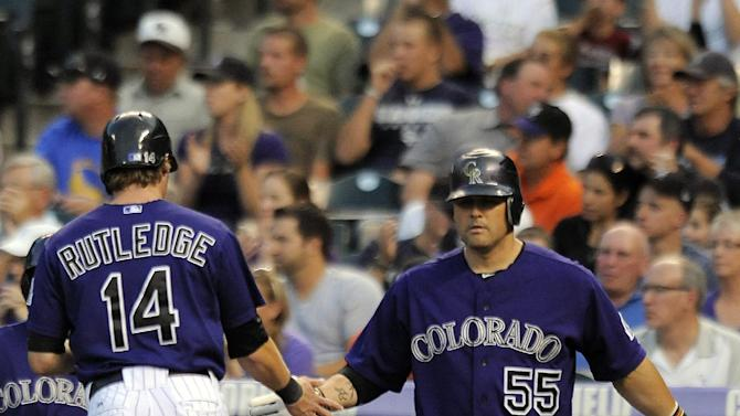 Colorado Rockies Ramon Hernandez, right, congratulates Josh Rutledge, left, after Rutledge scored on a single by Jordan Pacheco in the first inning of a baseball game against the San Francisco Giants in Denver on Monday, Sept. 10, 2012. (AP Photo/Chris Schneider)