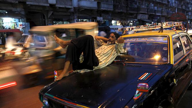 Vehicles move past a man resting on a taxi in Karachi