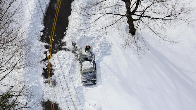 A person digs out a can near Hamden, Conn., Sunday, Feb. 10, 2013, in the aftermath of a storm that hit Connecticut and much of the New England states. (AP Photo/Craig Ruttle)