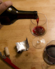 A bottle of red wine is poured into a glass.