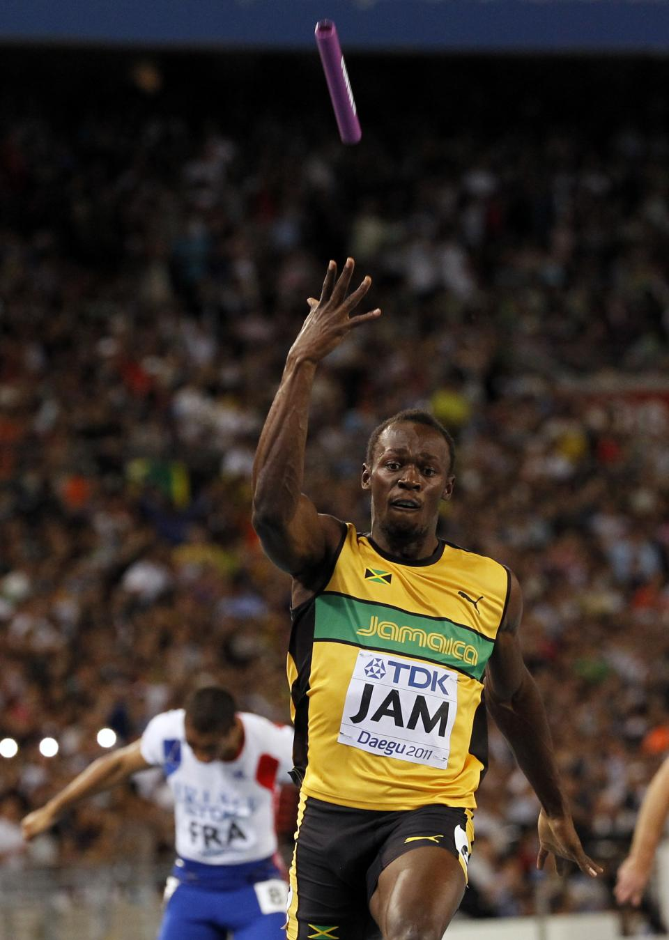 Jamaica's Usain Bolt throws the baton into the air as he crosses the finish line to win the Men's 4x100 Relay final and break a world record at the World Athletics Championships in Daegu, South Korea, Sunday, Sept. 4, 2011. (AP Photo/Anja Niedringhaus)