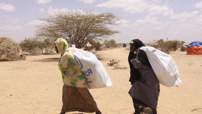 Southern Somali women carry food aid donations from the UNHCR, as they make their way to their refugee camp in Dollow, Somalia, Tuesday. Aug. 30, 2011.  Despite the drought and famine, refugees in Somalia are celebrating the Muslim holiday of Eid al-Fitr with the food rations distributed by aid agencies for their survival. (AP Photo/Khalil Senosi)