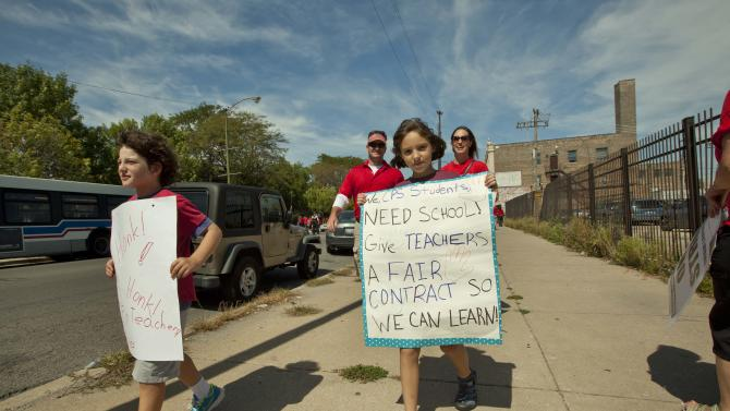 Children holding posters supporting striking teachers join a large group of public school teachers as they march on streets surrounding John Marshall Metropolitan High School on Wednesday, Sept. 12, 2012 in West Chicago. Teachers walked off the job Monday for the first time in 25 years over issues that include pay raises, classroom conditions, job security and teacher evaluations. (AP Photo/Sitthixay Ditthavong)