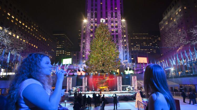People drink as they stand near the tree after the 81st Annual Rockefeller Center Christmas Tree Lighting Ceremony in New York