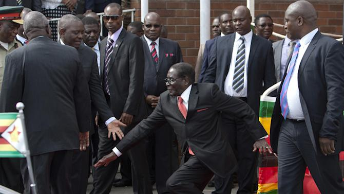 Zimbabwean President Robert Mugabe, center, falls after addressing supporters upon his return from an African Union meeting in Ethiopia, Wednesday, Feb. 4, 2015. Mugabe, 90, was elected chairman of the African Union and is set to celebrate his 91st birthday on Feb. 21. (AP Photo)