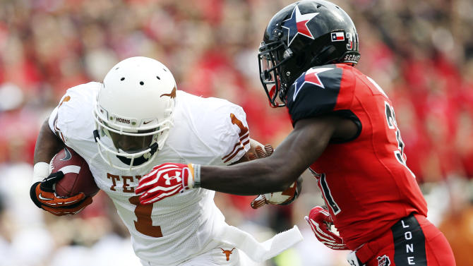 Texas' Mike Davis makes a catch ahead of Texas Tech's Eugene Neboh during their NCAA college football game, Saturday, Nov. 3, 2012, in Lubbock, Texas. (AP Photo/Lubbock Avalanche-Journal,Stephen Spillman)  LOCAL TV OUT