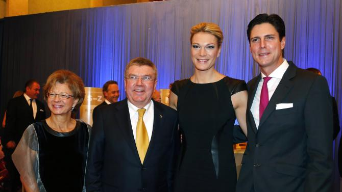 """IOC President Bach, his wife Claudia, Germany's former Alpine Skier Hoefl-Riesch and her husband Marcus pose for the media during their arrival for the """"Sportsmen of the Year"""" gala in Baden Baden"""