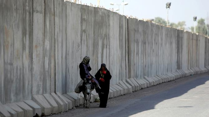 An Iraqi woman rides on a donkey as another follows close by, as they skirt a huge concrete blast wall protecting an Iraqi army camp, in the Ghazaliya district of Baghdad