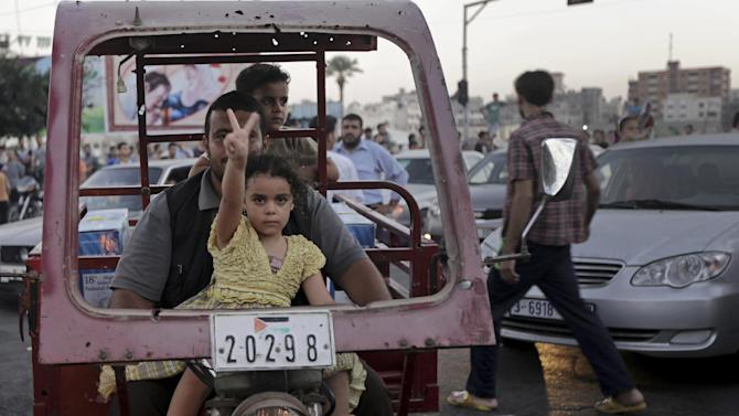 A Palestinian girl flashes victory sign with her father as they celebrate the cease-fire between Palestinians and Israelis at the main rood in Gaza, in the northern Gaza Strip, Tuesday, Aug. 26, 2014. Israel and Hamas agreed Tuesday to an open-ended cease-fire, halting a seven-week war that killed more than 2,200 people, the vast majority Palestinians, left tens of thousands in Gaza homeless and devastated entire neighborhoods in the blockaded territory. (AP Photo/Adel Hana)