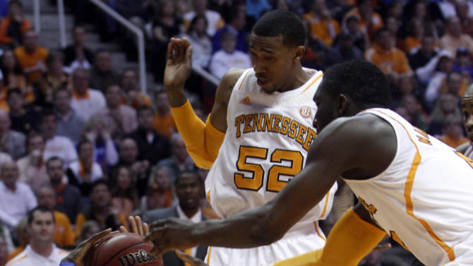 Kentucky guard Archie Goodwin (10) falls to the floor as he's defended by Tennessee guard Jordan McRae (52) and center Yemi Makanjuola (0) in the first half of an NCAA college basketball game on Saturday, Feb. 16, 2013, in Knoxville, Tenn. (AP Photo/WADE PAYNE)