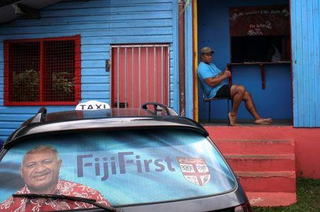 Election poster for Bainimarama can be seen in the rear window of a taxi as a man gestures from the doorway of a local gymnasium in the Fiji capital of Suva
