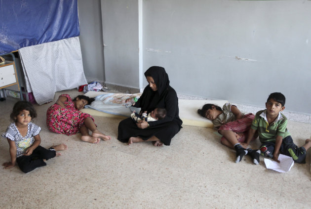 A Syrian refugee who identified herself as Um Ali sits with her children inside a government school in Marj, Lebanon, Monday, July 23, 2012. After a bloody, weeklong siege in the Syrian capital, Damascus, residents who stayed behind are facing hours-long queues for petrol and bread, stinking piles of rubbish in the streets and scenes of unimaginable destruction while thousands of Syrians have escaped to Lebanon over the past week. (AP Photo/Bilal Hussein)