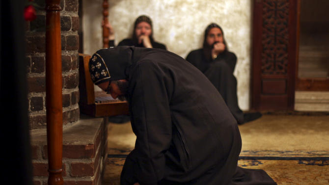 Clergymen pray during an early morning mass at the historic al-Muharraq Monastery, a centuries-old site some 180 miles (300 kilometers) south of Cairo in the province of Assiut, Egypt, Tuesday, Feb. 5, 2013. Egypt's Coptic Christian pope sharply criticized the country's Islamist leadership in an interview with The Associated Press on Tuesday, saying the new constitution is discriminatory and Christians should not be treated as a minority. (AP Photo/Khalil Hamra)