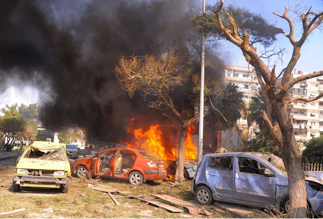 This photo released by the Syrian official news agency SANA, shows flames and smoke rising from burned cars after a huge explosion that shook central Damascus, Syria, Thursday, Feb. 21, 2013. A car bo