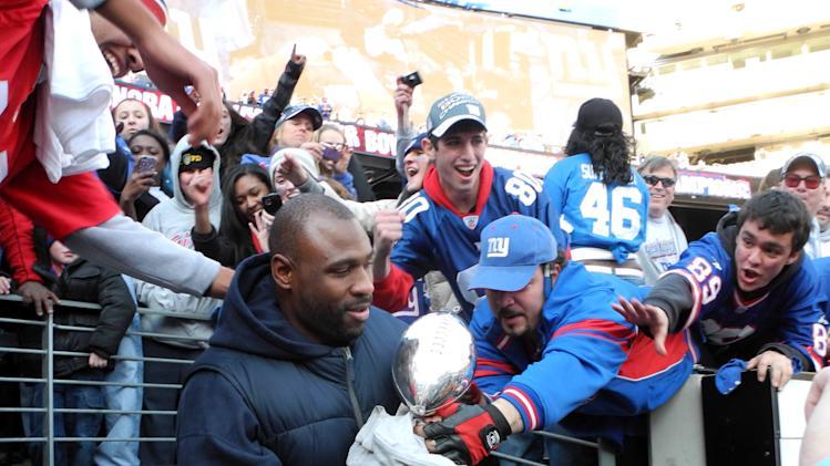 Fans reach out to touch the Vince Lombardi trophy held by New York Giants' Brandon Jacobs at a victory celebration rally at MetLife Stadium on Tuesday, Feb. 7, 2012, in East Rutherford, N.J. The Giants defeated the New England Patriots in Super Bowl XLVI on Sunday. (AP Photo/Bill Kostroun)