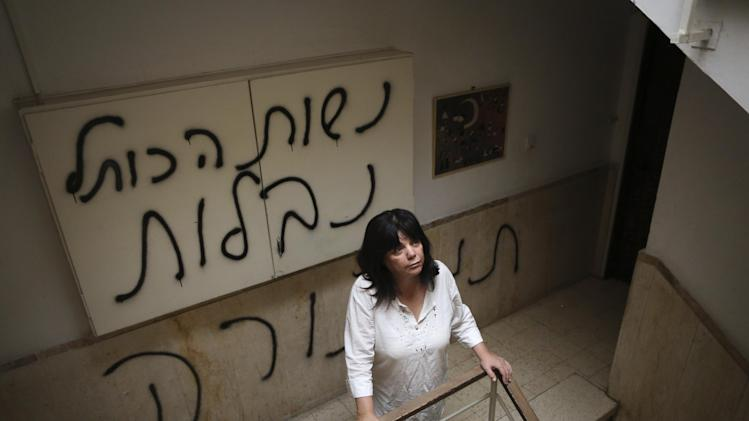 "Peggy Cidor, a leading member of the Women of the Wall organization, stands in the hallway of her building in Jerusalem, Monday, May 20, 2013. The group, known as ""Women of the Wall,"" convenes monthly prayer services at the Western Wall, the holiest site where Jews can pray, wearing prayer shawls and performing rituals that ultra-Orthodox Jews believe only men are allowed to do. Israeli officials initially opposed the group but have recently backed its right to worship and earlier this month thousands of ultra-Orthodox protesters tried to prevent their prayer service. The graffiti in Hebrew reads, ""The women of the Western Wall are despised."" (AP Photo/Michal Fattal) ***ISRAEL OUT***"