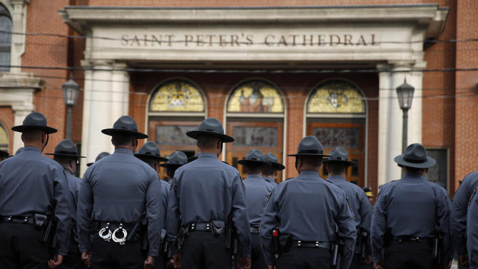 Law enforcement officers gather outside before a funeral service for Pennsylvania State Trooper Cpl. Bryon Dickson, Thursday, Sept. 18, 2014, in Scranton, Pa. Dickson was killed on Friday night in an ambush shooting at the state police barracks in Blooming Grove Township. Authorities are looking for 31-year-old Eric Frein, of Canadensis, who is charged with killing one trooper and wounding another outside the barracks. (AP Photo/Matt Slocum)