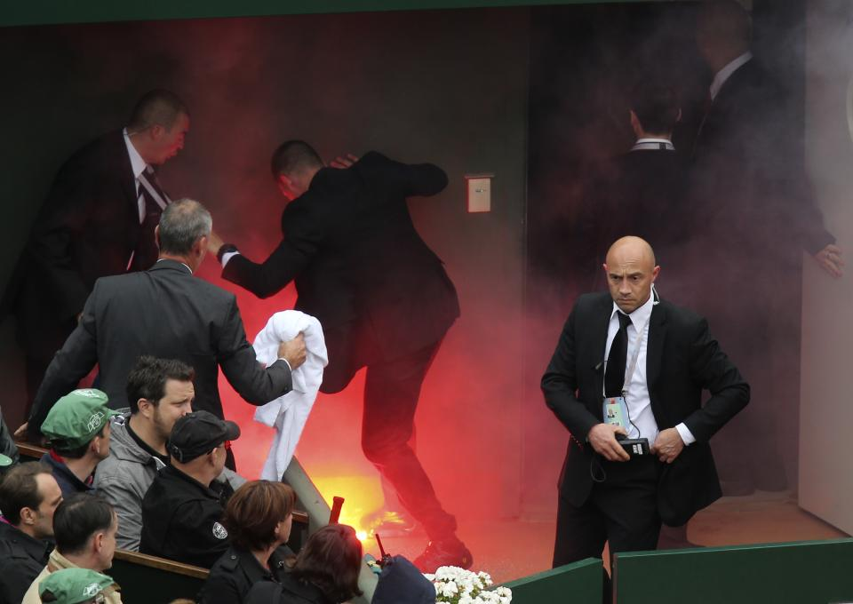 Security officer try to put out a fire after a demonstrator ran onto center court with flares as Spain's Rafael Nadal plays compatriot David Ferrer during the men's final match of the French Open tennis tournament at the Roland Garros stadium Sunday, June 9, 2013 in Paris. (AP Photo/David Vincent)