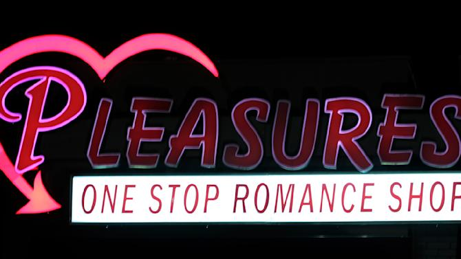 """The Pleasures sign flickers over the old bank building in Huntsville, Ala., Saturday, Dec.18, 2010. The """"romance"""" store features what's billed as the nation's first drive-thru with adult novelties for sale. Business is brisk so far, with cars sometimes lining up three deep for vibrators, lubricants, lingerie and other risque items. (AP Photo/Dave Martin)"""