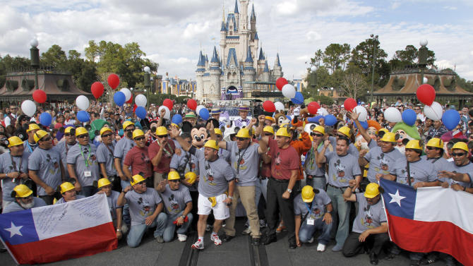 FILE - In this Jan. 31, 2011 file photo, a group of the rescued Chilean miners pose for a group picture in front of the Magic Kingdom Castle during their visit to Walt Disney World in Orlando, Fla.. One of the myths surrounding the 33 miners who survived 69 days, 700 feet deep, and whose unprecedented and dramatic rescue was beamed to millions around the world, is that they are millionaires and do not need work. A year after the tragedy, nearly half are unemployed, one lives the fame that began to take shape at the bottom of the mine, many have chosen to give motivational talks to make a living and and four returned to work in the mines. (AP Photo/Reinhold Matay, File)