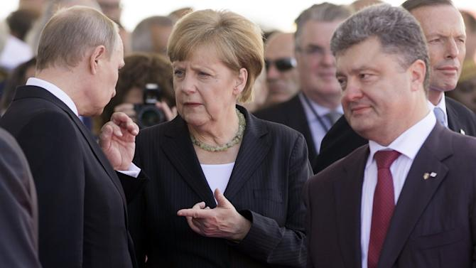 German Chancellor Angela Merkel speaks with Russian President Vladimir Putin (L) as Ukraine's President Petro Poroshenko (R) walks past in Ouistreham, France, June 6, 2014