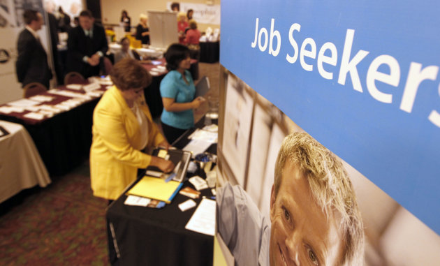 In this Tuesday, July 10, 2012 photo, people walk by the recruiters at a jobs fair in the Pittsburgh suburb of Green Tree, Pa. The number of people seeking unemployment benefits plunged last week to the lowest level in four years, a hopeful sign for the struggling job market. But the decline was partly due to temporary factors. (AP Photo/Keith Srakocic)