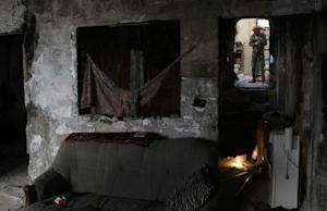 A Syrian rebel stands with his weapon in a room of…