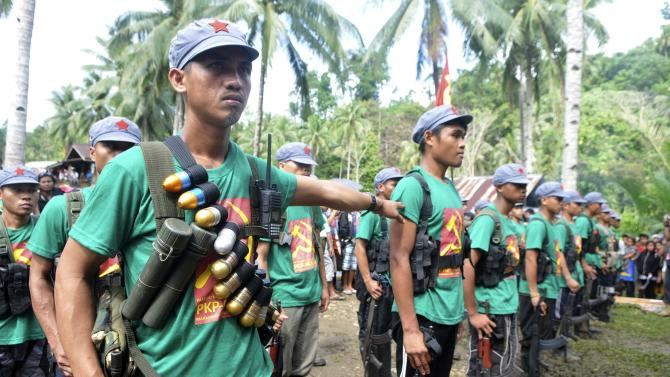 Members of the New People's Army rebels stand in attention during the 46th anniversary celebration of the Communist Party of the Philippines at a Marihatag town, Surigao del sur