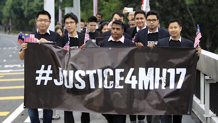 A youth group holds a banner as they march towards the Parliament house during a rally to seek justice for the victims of the Malaysia Airlines Flight 17, in Kuala Lumpur, Malaysia, Wednesday, July 23, 2014. A team of Malaysian investigators visited the site along with members of the the Organization for Security and Cooperation in Europe (OSCE) mission in Ukraine for the first time since the air crash last week. (AP Photo/Lai Seng Sin)