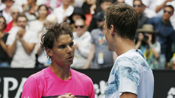 Tomas Berdych (R) of the Czech Republic shakes hands with Rafael Nadal of Spain after defeating him in their men's singles quarter-final match at the Australian Open 2015 tennis tournament in Melbourne
