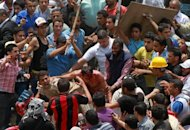 Egyptian protesters beat a man (C) who they accused of attacking them in the Abbassiya district in Cairo. Thugs attacked an anti-military protest near the defence ministry in Cairo on Wednesday, sparking clashes which killed 20 people in the politically tense run-up to Egypt's first post-uprising presidential poll