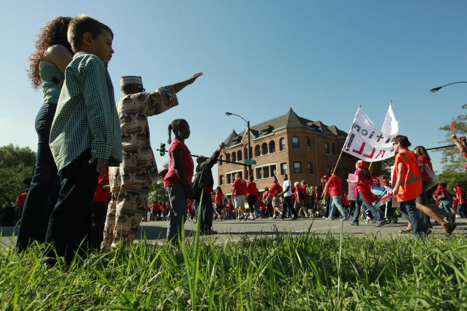 Residents of a west side Chicago neighborhood watch public school teachers march after a rally Saturday, Sept. 15, 2012 in Chicago. (AP Photo/Sitthixay Ditthavong)