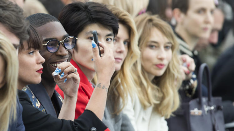 Singer Lily Allen, left, adjusts her make up and she sits next to singer Tinie Tempah, second from left, as they watch the Louis Vuitton men's Fall-Winter 2014-2015 fashion collection, presented Thursday, Jan. 16, 2014 in Paris. (AP Photo/Jacques Brinon)
