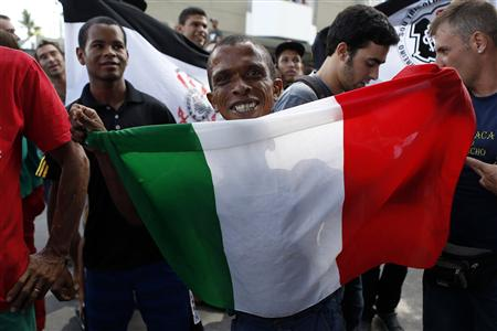 A fan of Italy holds a his team's flag as they arrive at their hotel at Recife city