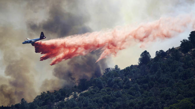 A bomber drops retardant on a wildfire in Mount Diablo State Park on Monday, Sept. 9, 2013 in Contra Costa County, Calif. A wildfire burning outside Mount Diablo State Park has forced dozens of residents and animals to evacuate Monday. (AP Photo/Marcio Jose Sanchez)