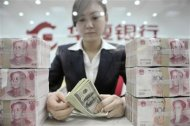 File photo of an employee counting U.S. dollar banknotes at a branch of Huaxia Bank in Shenyang