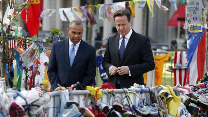 British Prime Minister David Cameron, right, and Massachusetts Gov. Deval Patrick visit the makeshift memorial to the Boston Marathon bombing victims in Copley Square in Boston, Tuesday, May 14, 2013. (AP Photo/Michael Dwyer)