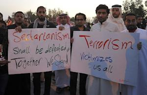 "Saudi mourners hold posters reading ""Sectarianism …"