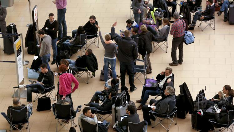 Passengers sit on chairs after flights were cancelled due to storm at airport Fuhlsbuettel in Hamburg