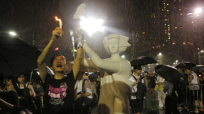 A man holds candlelight in front of a replica of the Goddess of Democracy as tens of thousands of people attend a candlelight vigil under heavy rain at Victoria Park in Hong Kong Tuesday June 4, 2013 to mark the 24th anniversary of the June 4th Chinese military crackdown on the pro-democracy movement in Beijing. (AP Photo/Vincent Yu)