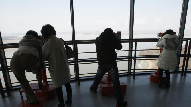 Visitors look at North Korea through binoculars a day after a cyberattack caused networks at major South Korean banks and top TV broadcasters to crash simultaneously, at the Unification Observation Post at in Paju near the demilitarized zone between the two Koreas, South Korea,Thursday, March 21, 2013. It's too early to assign blame - Internet addresses can easily be manipulated and the investigation could take weeks - but suspicion for Wednesday's shutdown quickly fell on North Korea, which has threatened Seoul and Washington with attack in recent days because of anger over U.N. sanctions imposed for its Feb. 12 nuclear test.  (AP Photo/Ahn Young-joon)