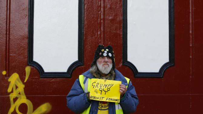 A man holds a sign during an anti-fracking protest in Preston